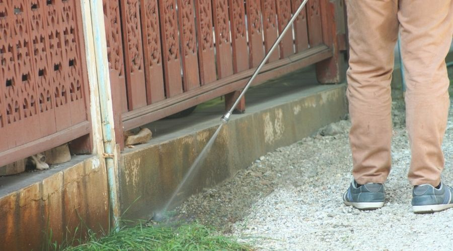 Texas pest control technician spraying liquid termite solution around the base of a building
