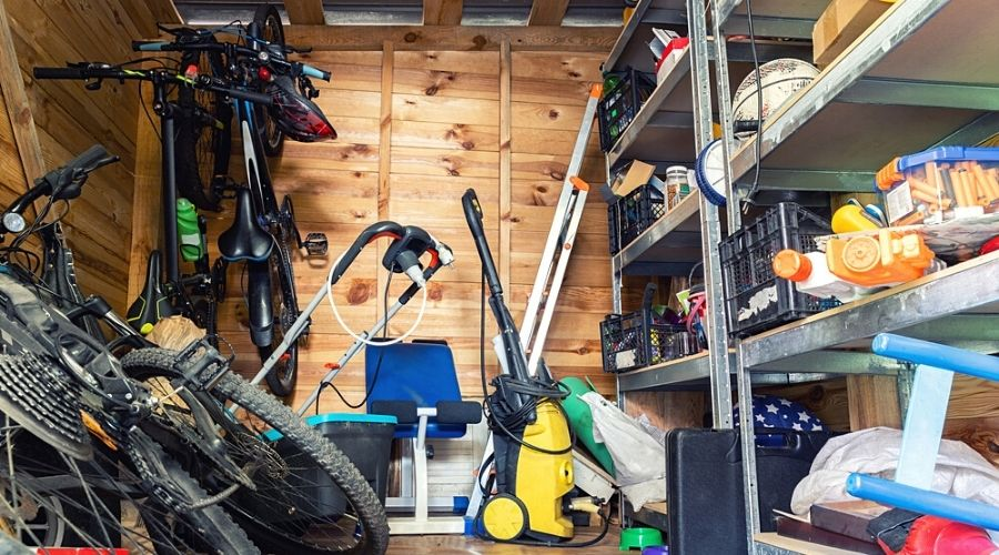 A cluttered garage with wood paneling.
