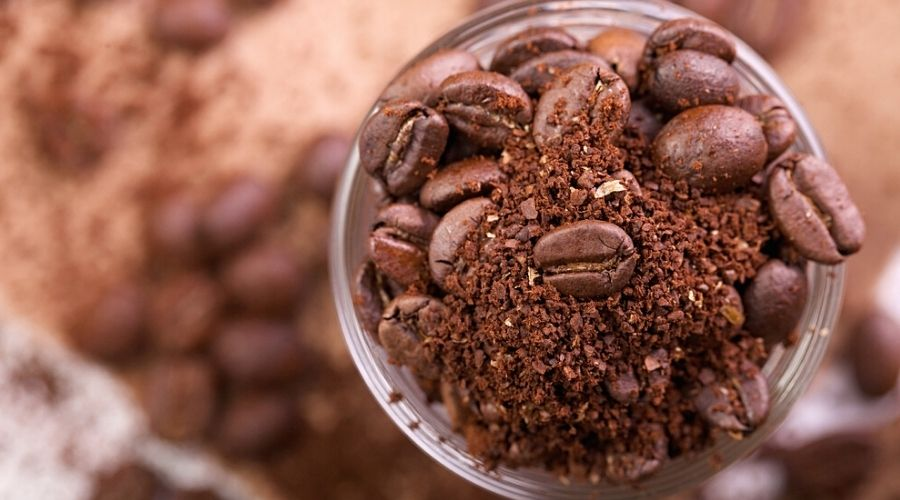 Top-down view of coffee grounds in a glass jar.